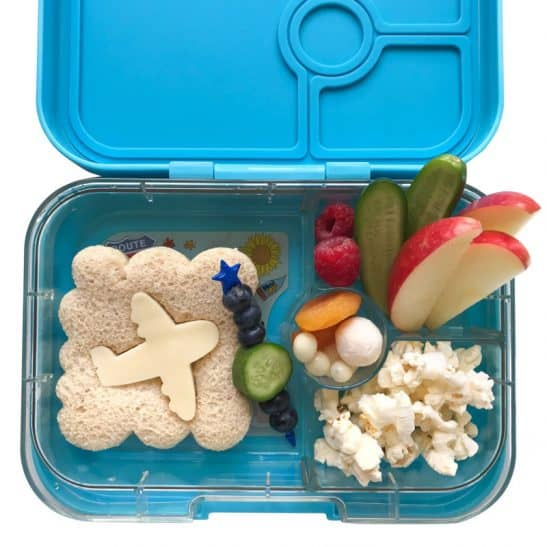 A lunch box filled with fruit, popcorn and an aeroplane shaped sandwich.