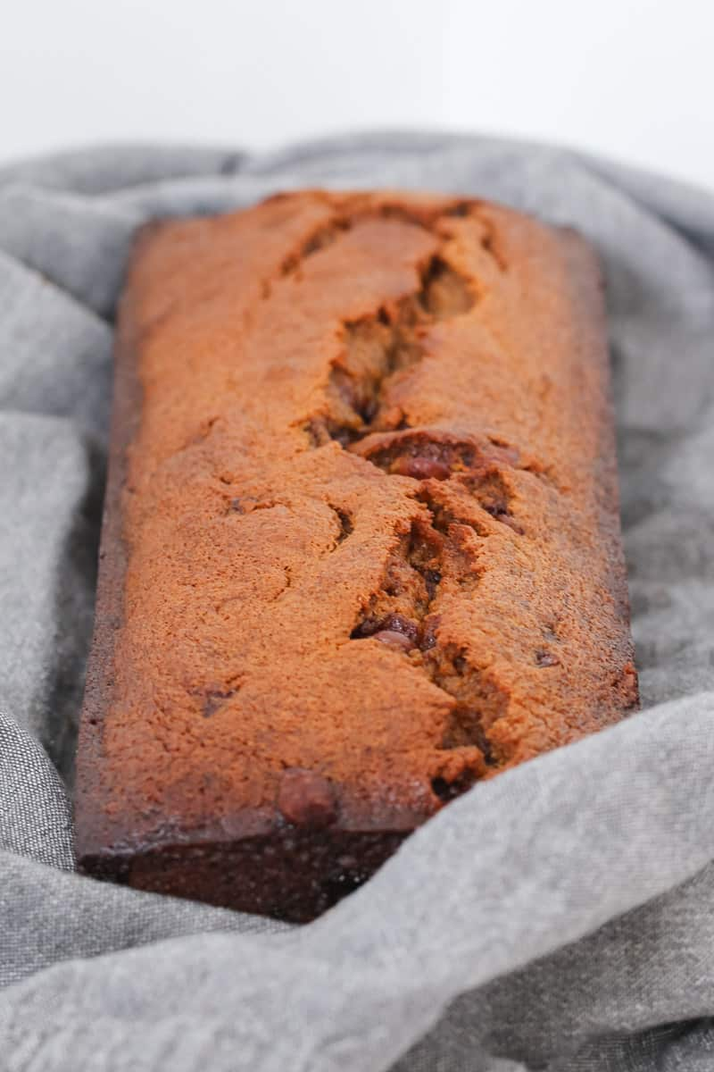 A loaf of banana bread with chocolate wrapped up in a tea towel.