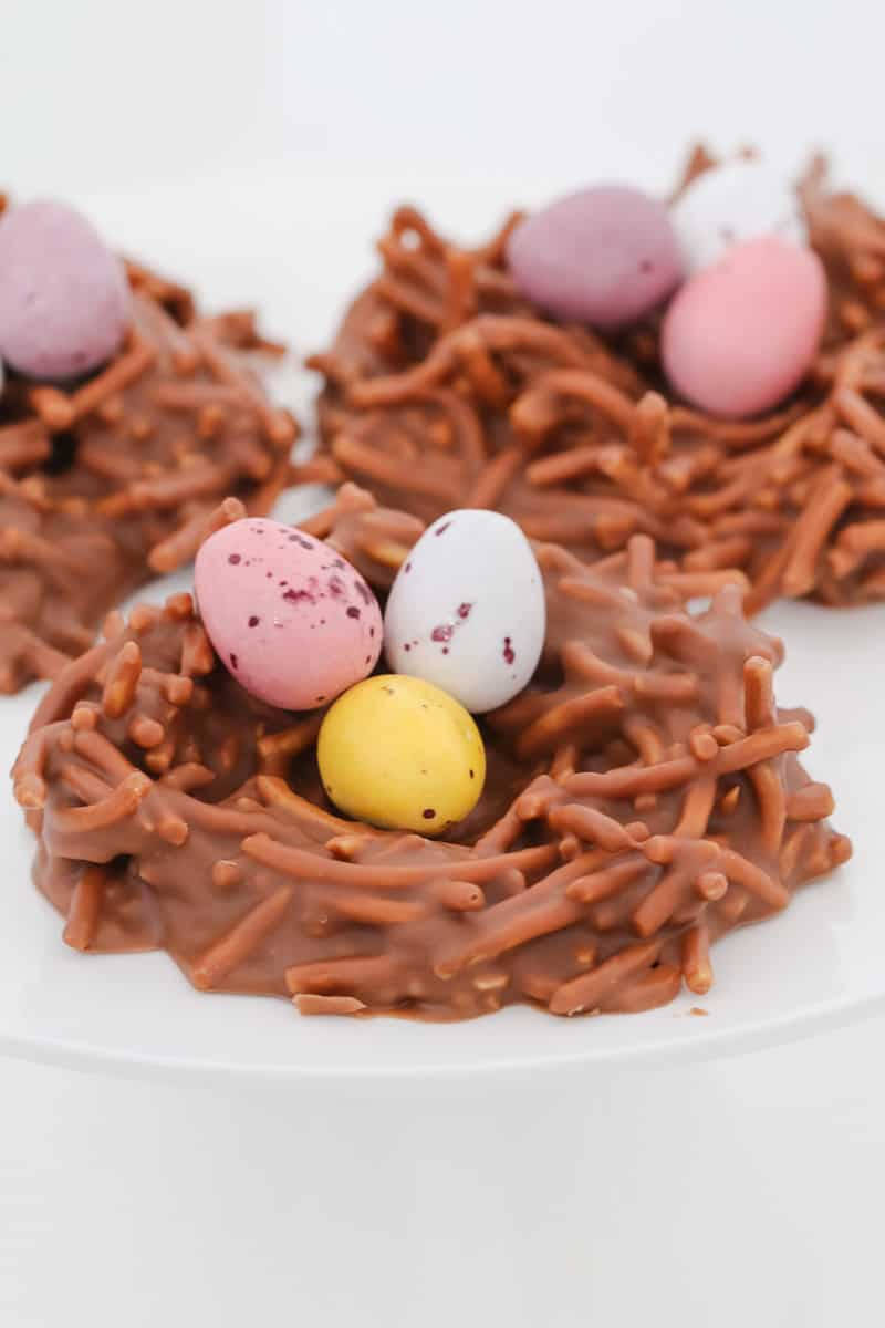 Easter eggs sitting inside chocolate noodle birds nests.