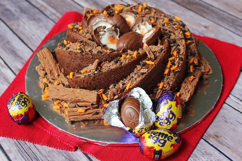 An easter chocolate bundt cake decorated with Flake chocolate bars and Cadbury creme eggs.