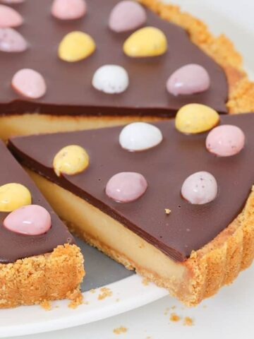 The most delicious Easter Chocolate Caramel Tart with a biscuit crumb base, creamy caramel filling, chocolate ganache topping and mini Easter eggs!