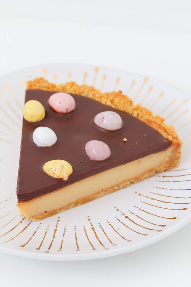 A piece of three layer caramel tart with chocolate ganache.