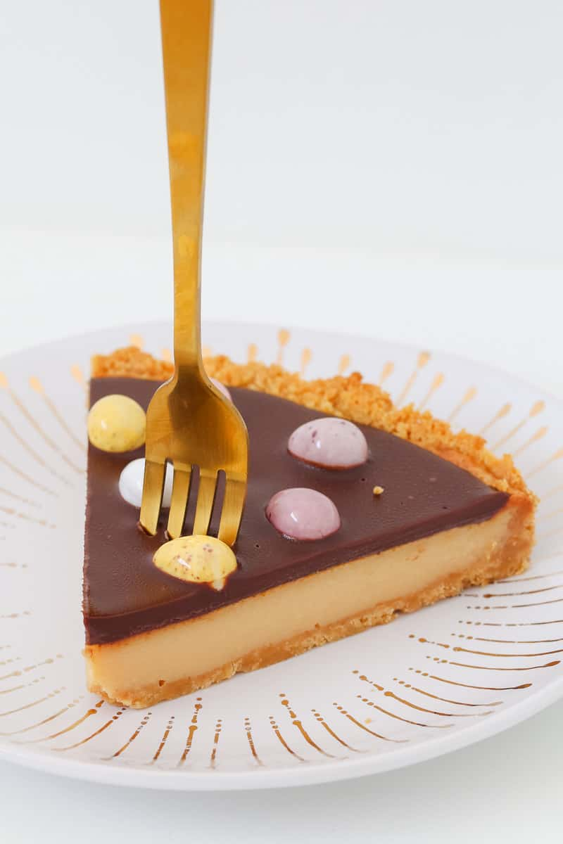 A fork in a piece of caramel tart with a chocolate ganache topping and mini easter eggs.