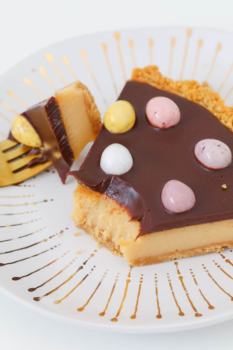 A piece of half-eaten chocolate caramel tart with Easter eggs on top.