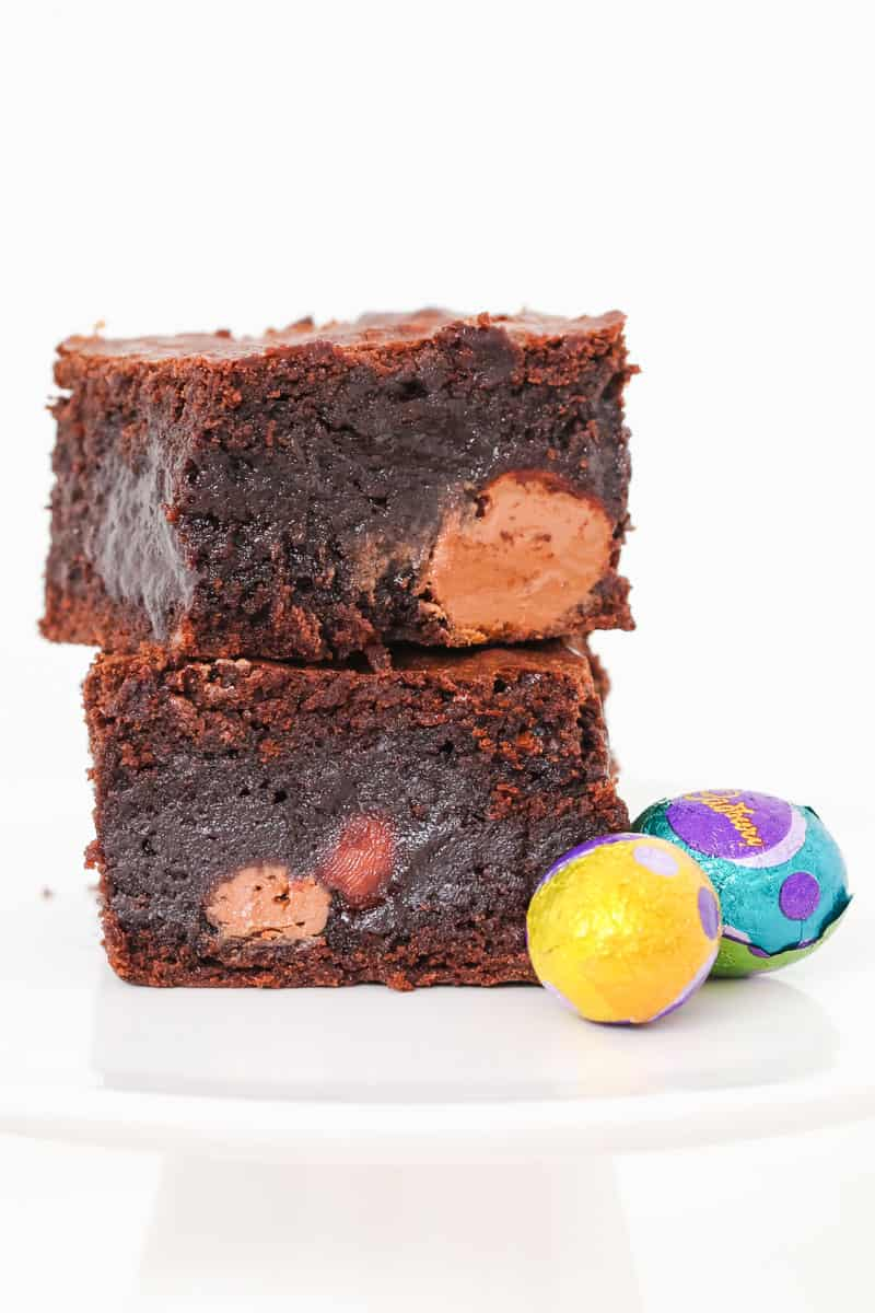 Easter eggs sitting next to two pieces of chocolate brownie.