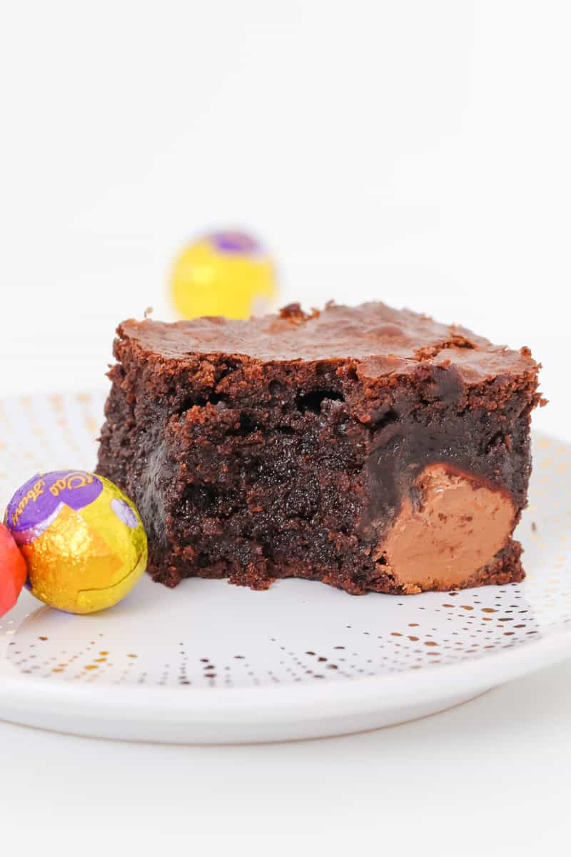 A half-eaten piece of moist chocolate brownie with Easter eggs inside.