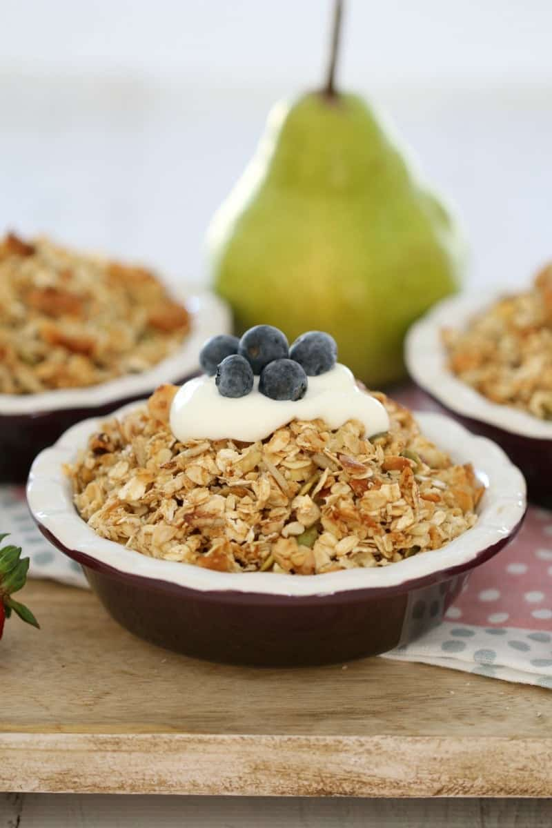 Pear and berry bowls topped with nut crumble, yoghurt and blueberries.