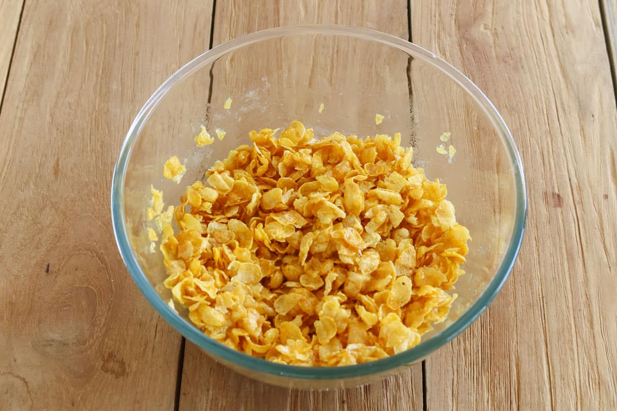 Cornflakes being added to a bowl of honey joy mixture.
