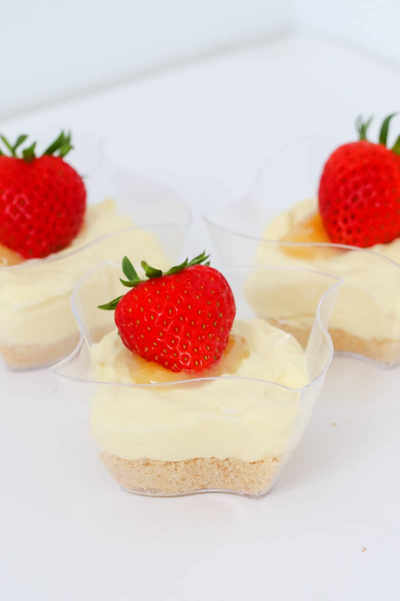 Lemon cheesecakes with a biscuit crumb base, creamy lemon filling, lemon curd and fresh strawberries.