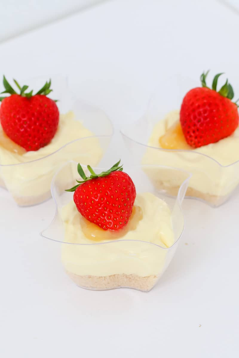 No bake lemon cheesecakes with lemon curd and fresh strawberries.