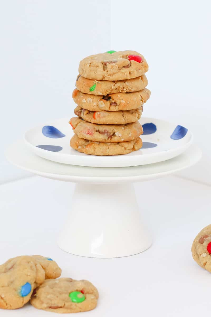 Peanut butter cookies on a plate with chocolate chips and M&Ms.