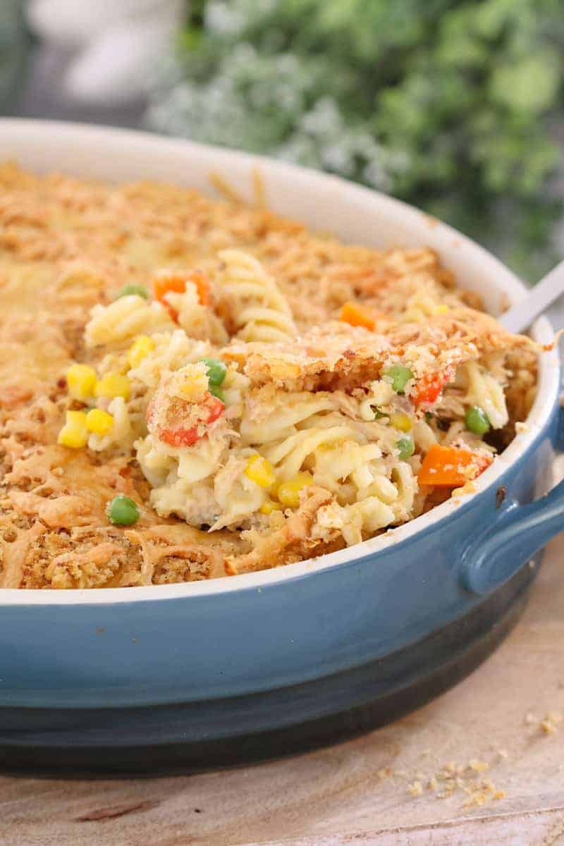 Pasta bake made with tuna, corn, peas and carrots being served from a baking dish.