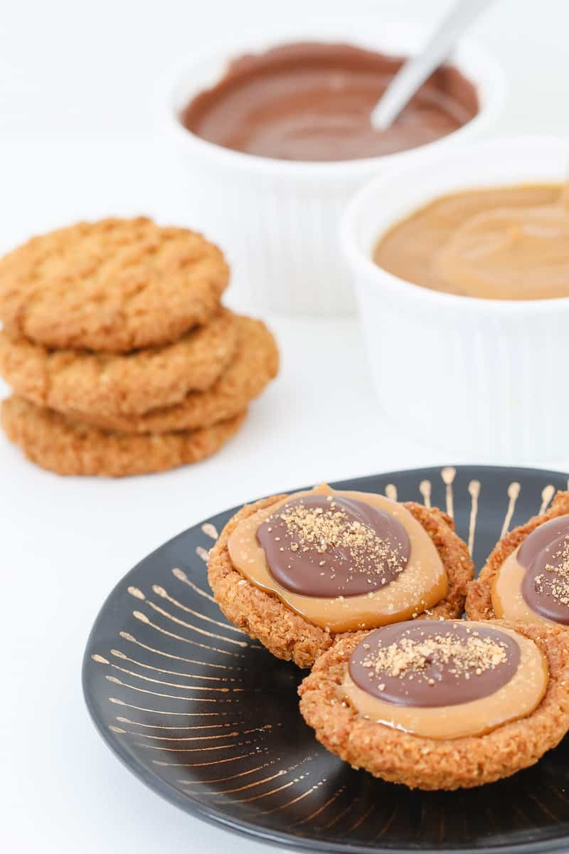 Biscuits in the background of chocolate caramel tartlets.