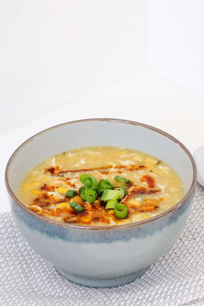 A bowl of chicken and corn soup with spring onions and soy sauce.