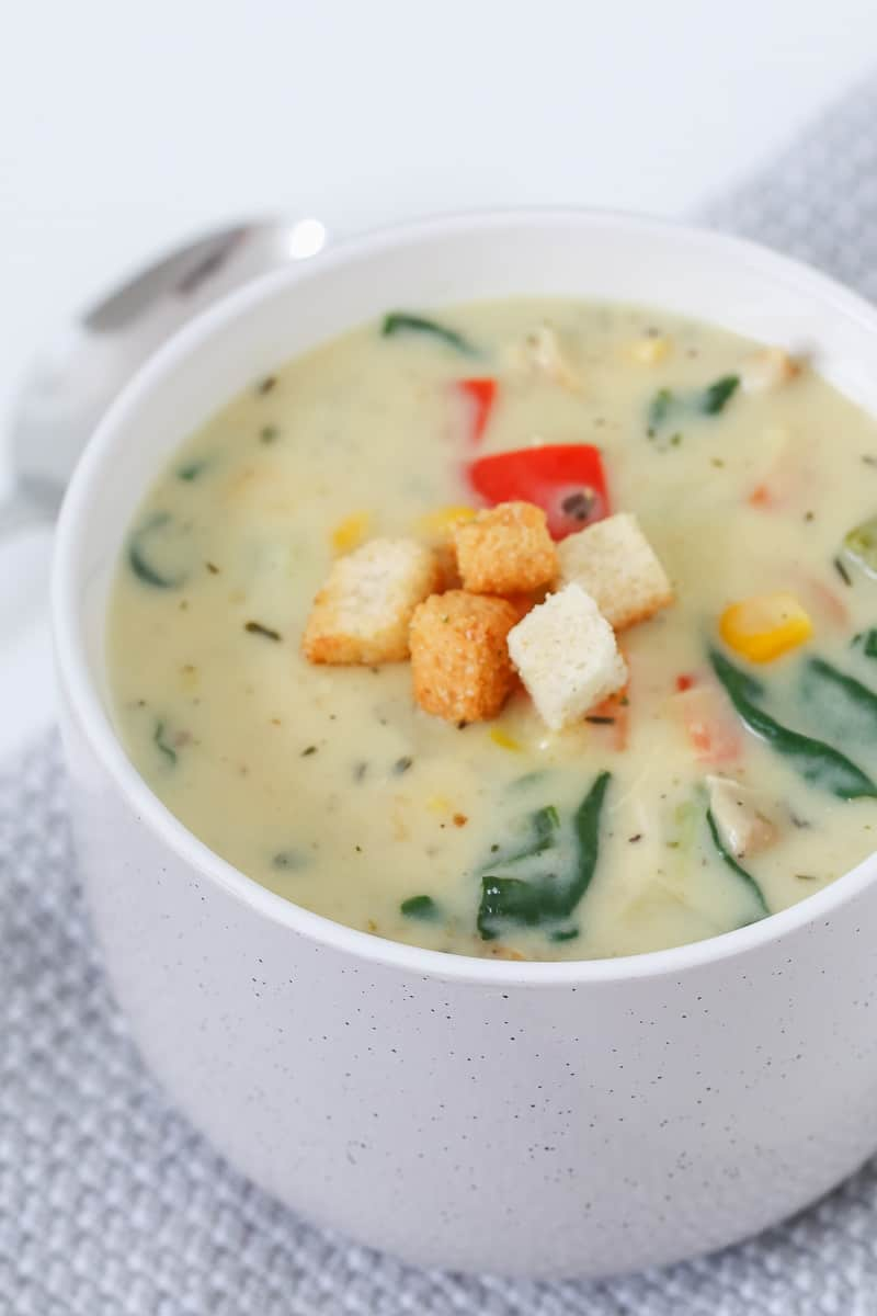 Spinach and vegetables in a cup of creamy soup.