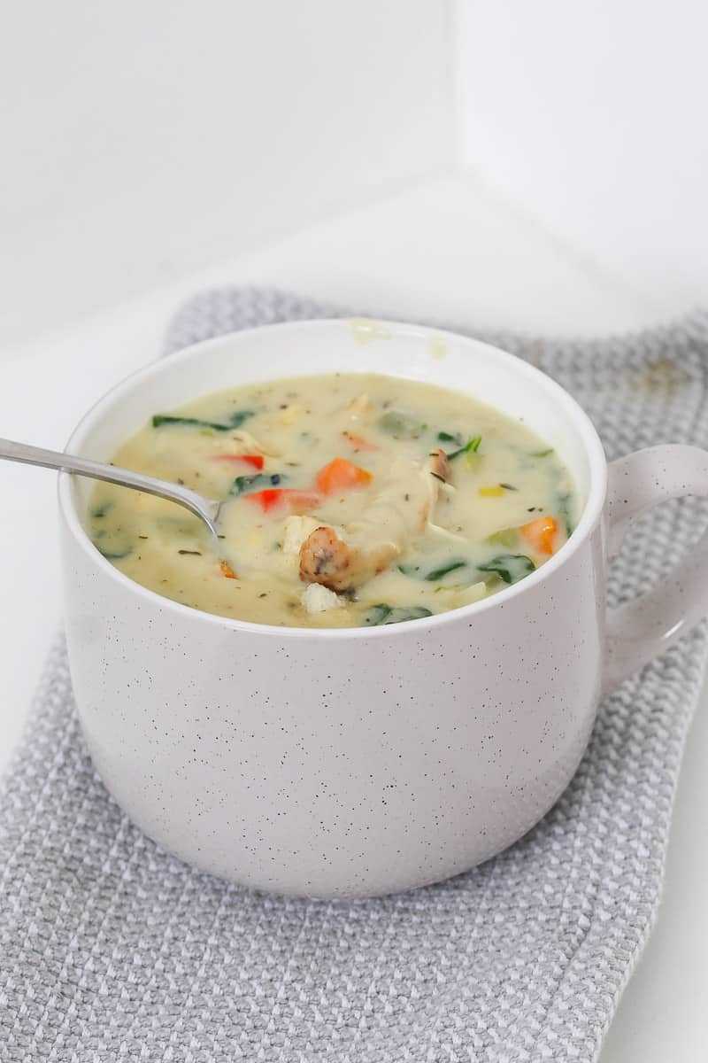 A cup of creamy soup with a spoon.