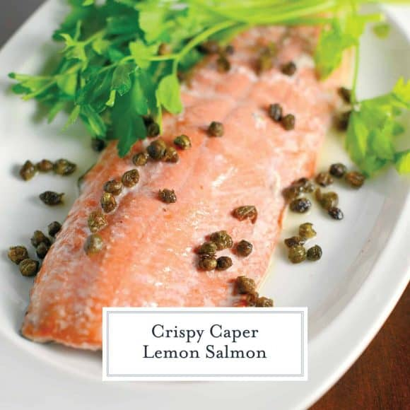 Images is of a large white platter with a whole baked salmon fillet topped with scattered capers and a sprig of parsley.