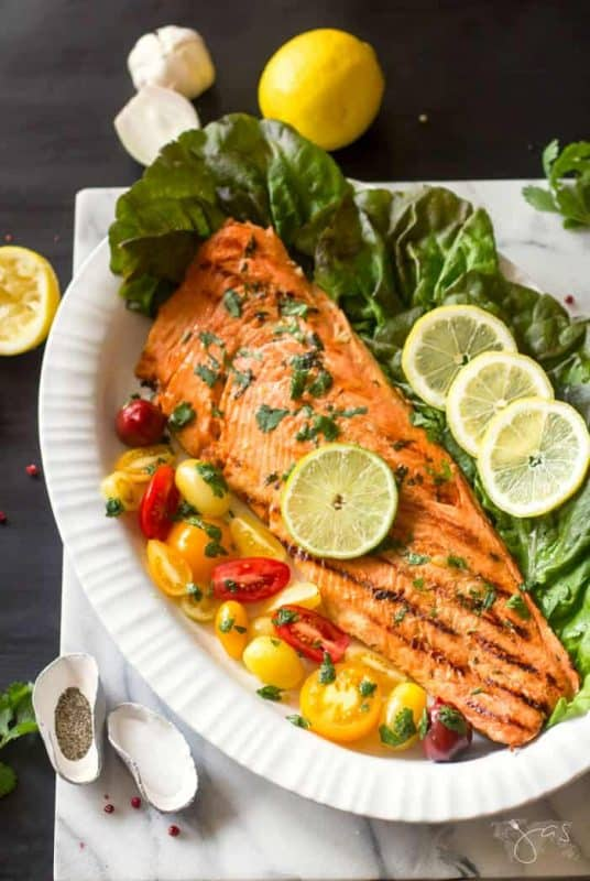 Image is of a large white platter with a whole large grilled salmon fillet garnished with grommet mini tomatoes, and sliced lemon on a bed of lettuce leaves.