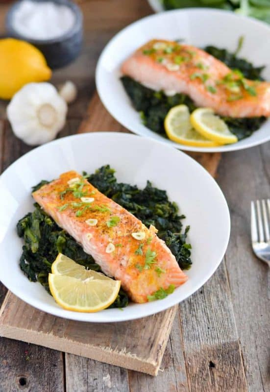 Image is of two white plates, both containing a baked salmon fillet on a bed of cooked spinach leaves, garnished with garlic, spring onion and lemon wedges.