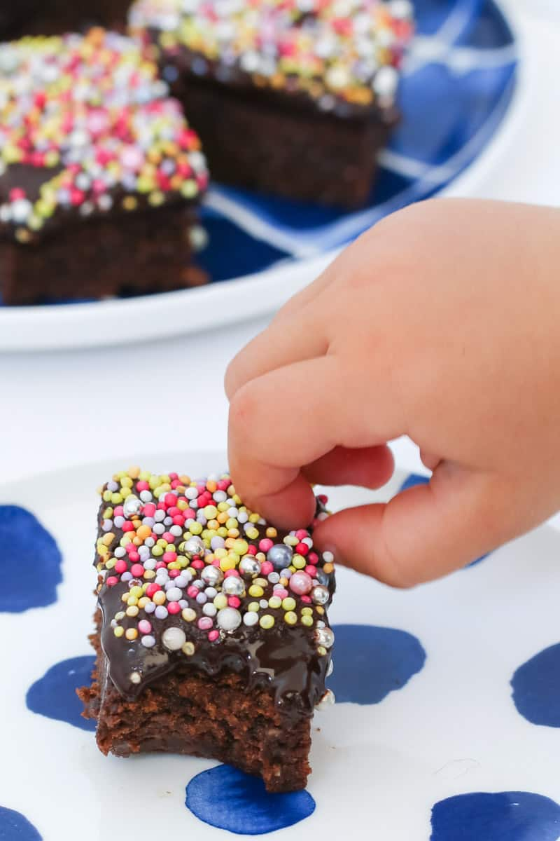 A kids hand taking sprinkles off the top of a chocolate slice.