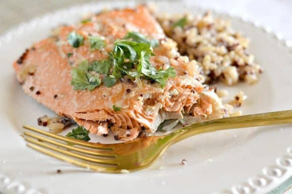 Image is of a white plate with a gold fork resting on it. On the plate is a baked salmon filled on a bed of brown rice garnished with cracked pepper and parsley leaves.