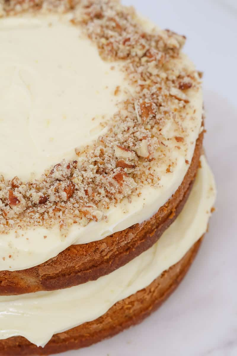 Pecans and cream cheese icing on a cake.