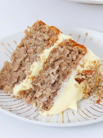 A slice of hummingbird cake on a white plate