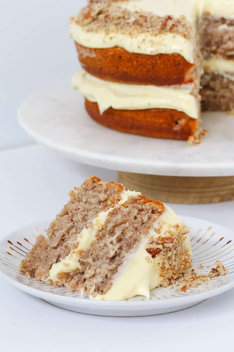 A slice of two layer banana, pineapple and pecan cake with frosting.