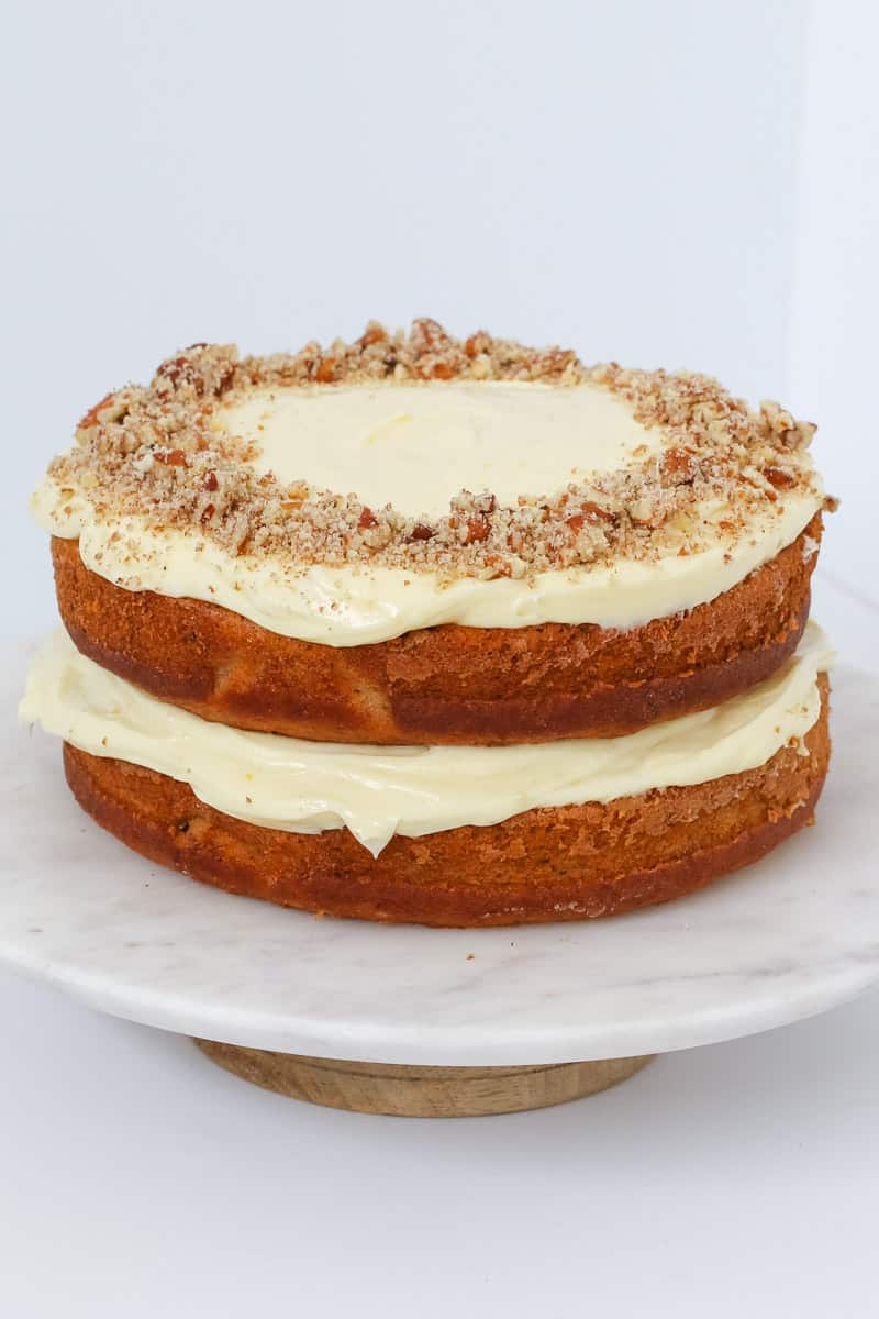 A two layer cake filled with cream cheese frosting and topped with chopped pecans.