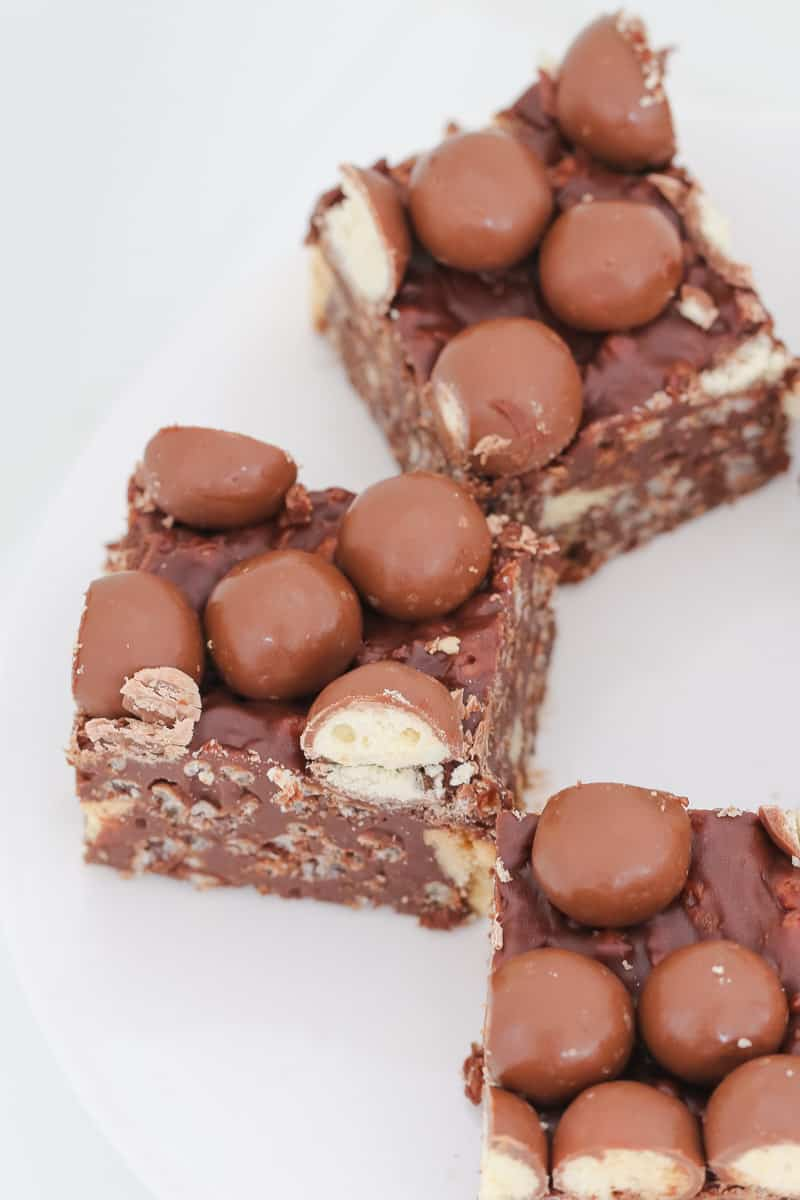 Pieces of no-bake chocolate slice with biscuits and Maltesers.