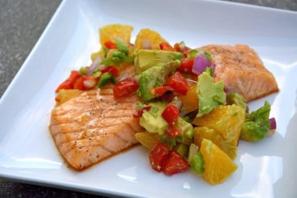 Image of a square white plate with a baked salmon fillet topped with a chunky green, red and orange salsa.