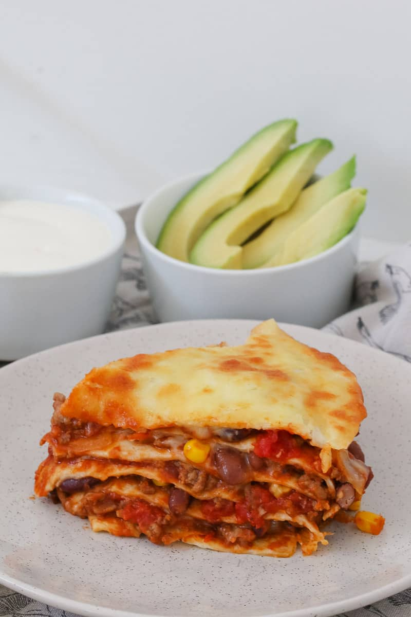 Avocado and sour cream behind a stack of corn, beef, mince, tortillas and cheese in a lasagne.