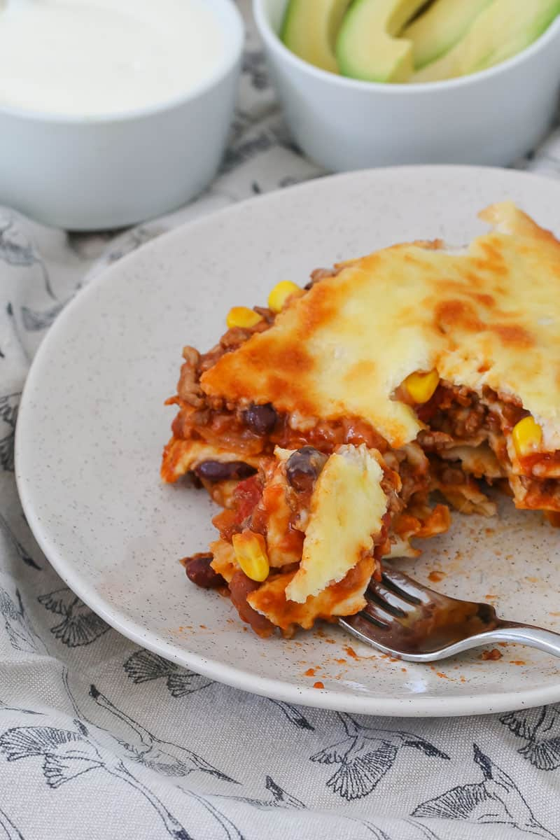 A plate of half-eaten lasagne made with tortillas and beans.