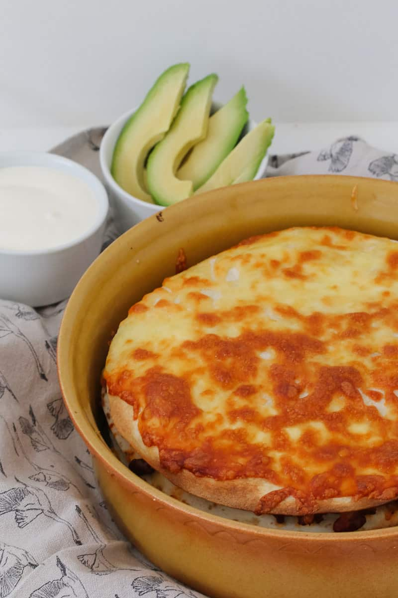 A baking dish of mexican beef lasagne with avocado and sour cream.