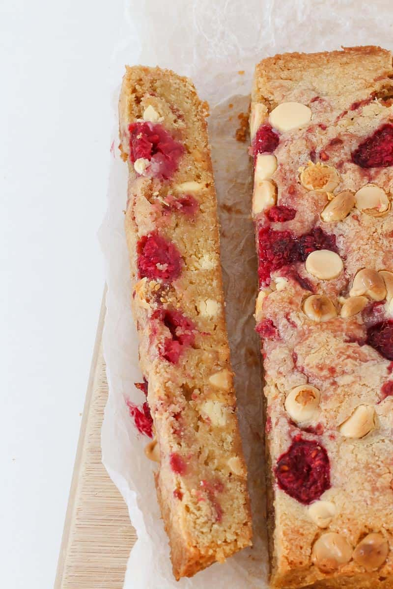 A long piece of a baked raspberry slice.