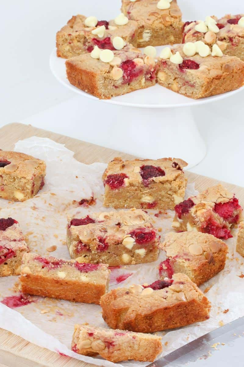 A raspberry blondie slice being cut on a chopping board.