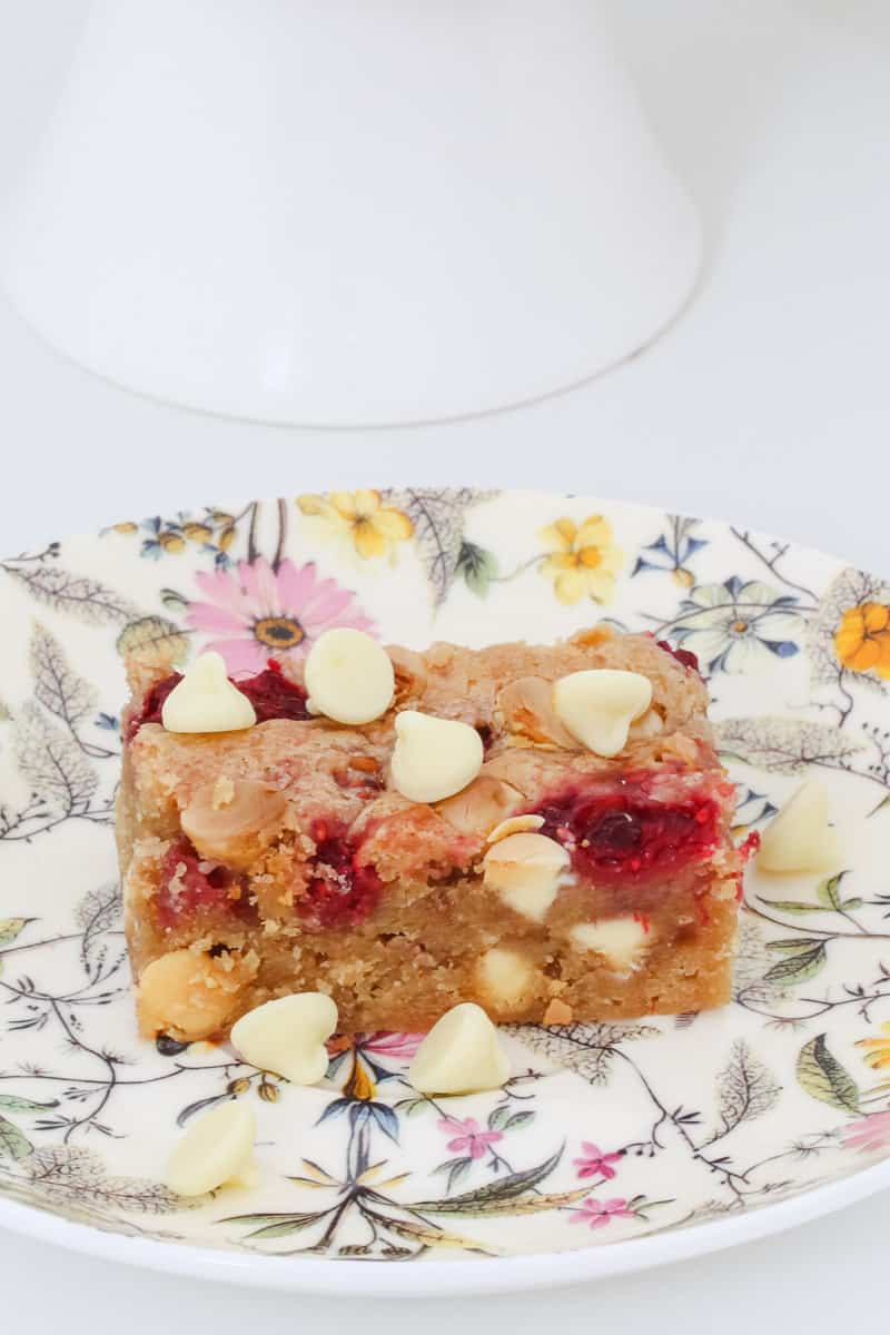 A piece of raspberry and white chocolate blondie on a floral plate.