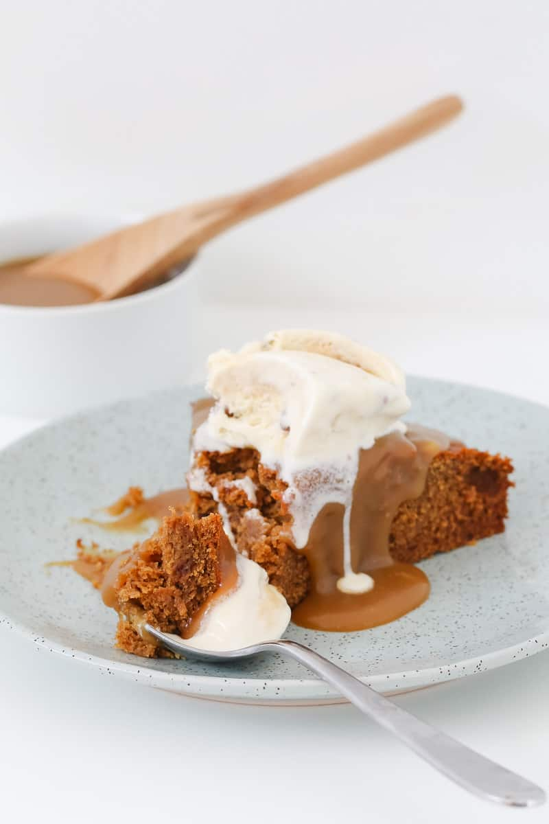 Ice-cream and caramel sauce on top of a spoonful of sticky date pudding.
