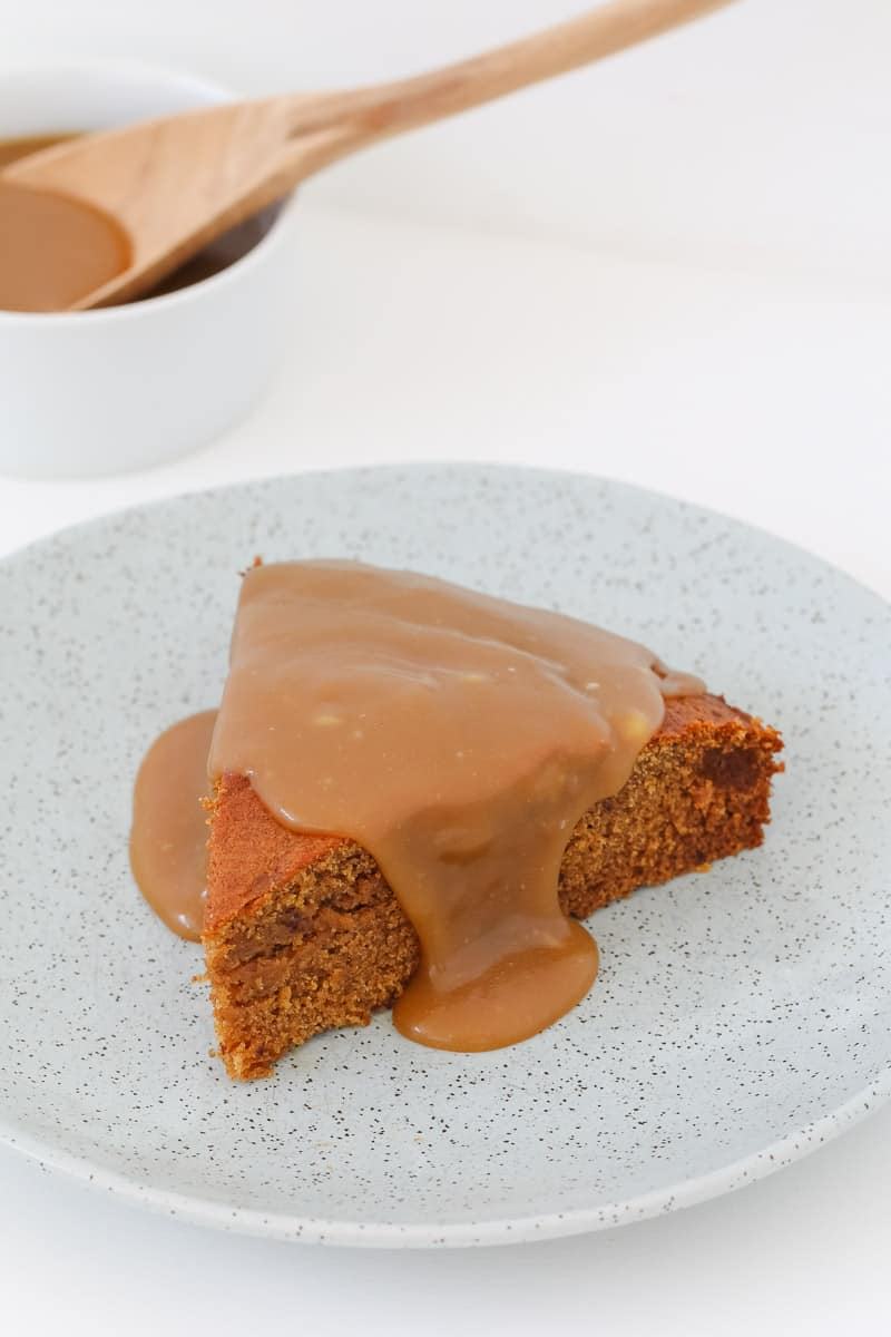 Caramel sauce oozing down the sides of a slice of sticky date pudding.