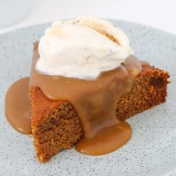 A slice of Sticky Date Pudding drizzled with caramel sauce and topped with vanilla ice cream on a plate.