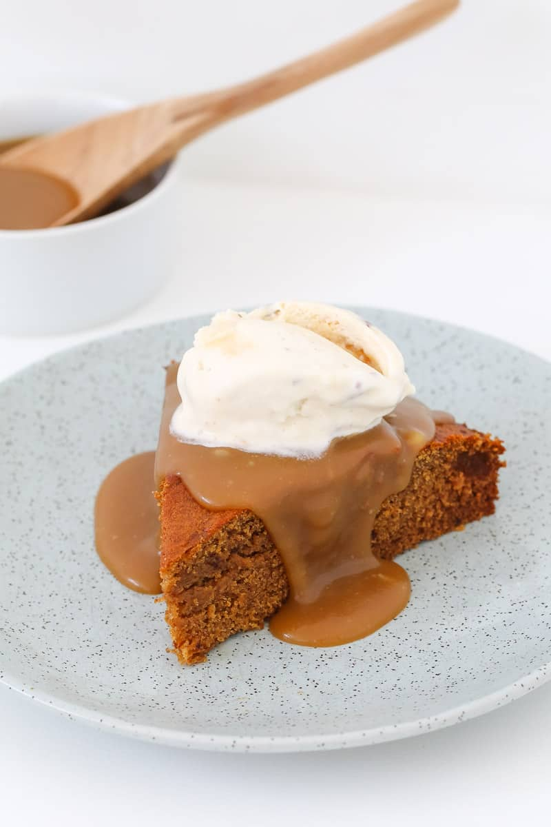 Caramel sauce drizzling down the sides of a piece of sticky date pudding with ice-cream.