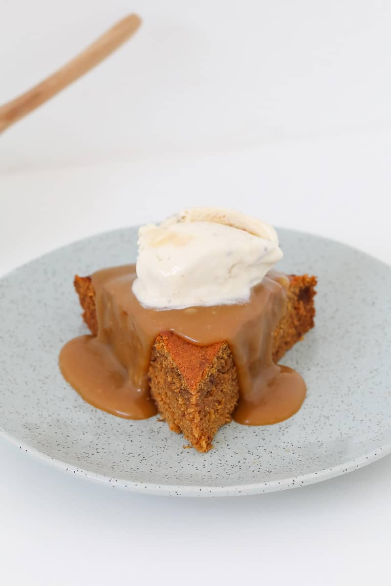 A scoop of ice-cream and drizzled homemade caramel sauce over the top of sticky date pudding.