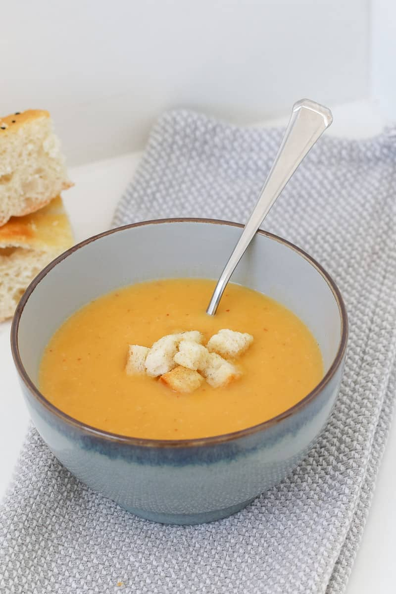 A spoon and bowl of pumpkin soup with croutons.