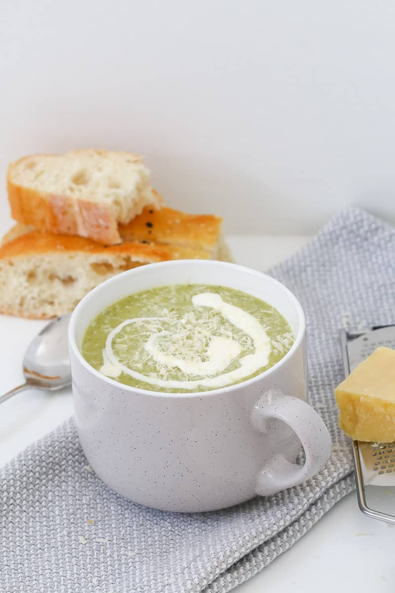 Bread in the background and a cup of cream swirled green soup.