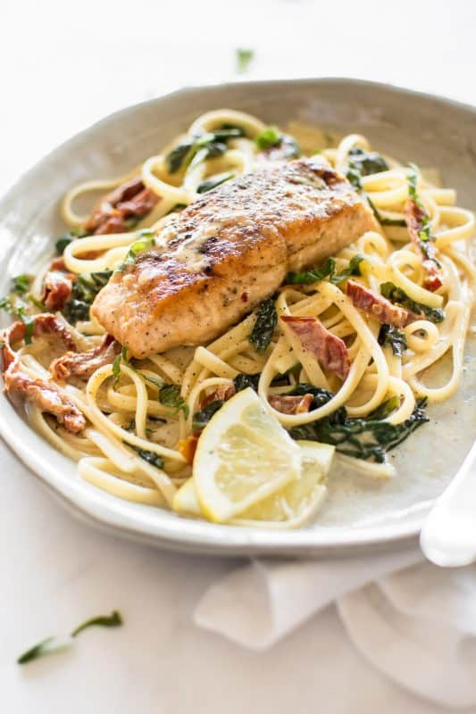 Image is of a white plate with a delicious looking linguine pasta tossed with sun-dried tomatoes and baby spinach topped with a baked salmon fillet.