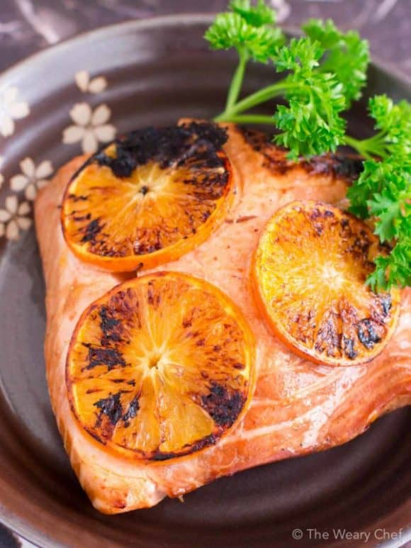 Image of black plate with a full square salmon fillet topped with four slices of orange and garnished with parsley.