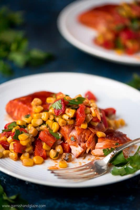 Image is of a white plate with a baked salmon fillet topped with corn and diced capsicum and parsley.
