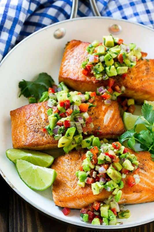 Image is of a white bowl filled with three salmon fillets topped with chopped avocado, tomatoes and herbs garnished with lime wedges and parsley leaves.