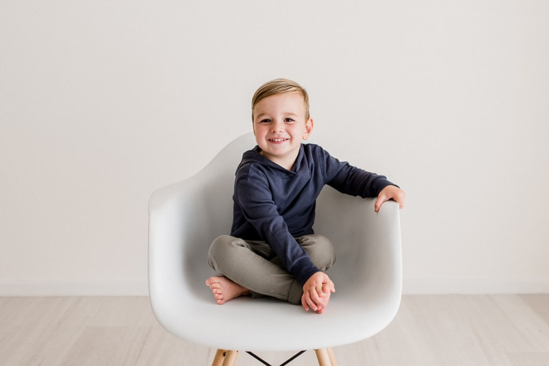 A young boy sitting on a white chair smiling.