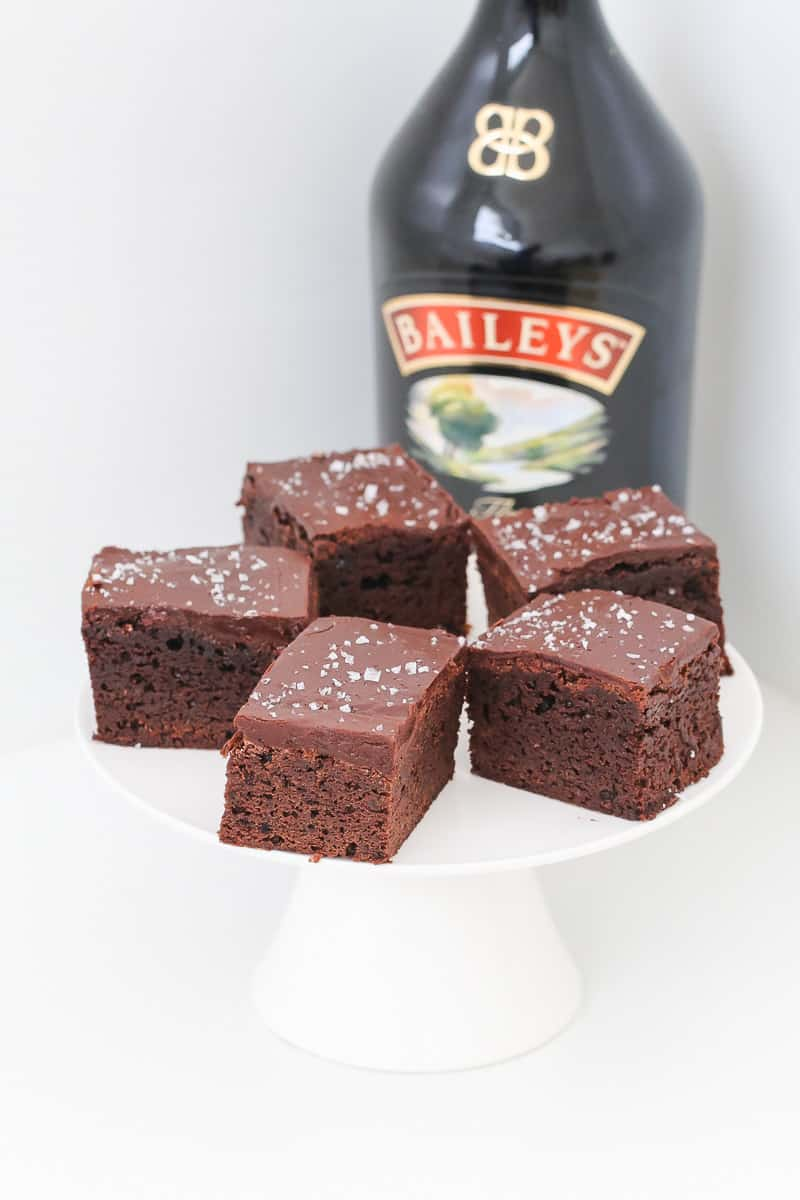 A cake stand with chocolate frosted brownies with a bottle of Baileys in the background.